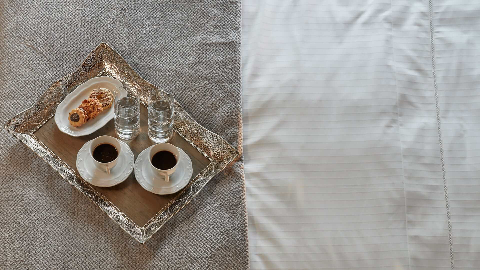 Coffee tray on luxury bed sheets in one of the Domus Renier Boutique Hotel rooms & suites in Chania