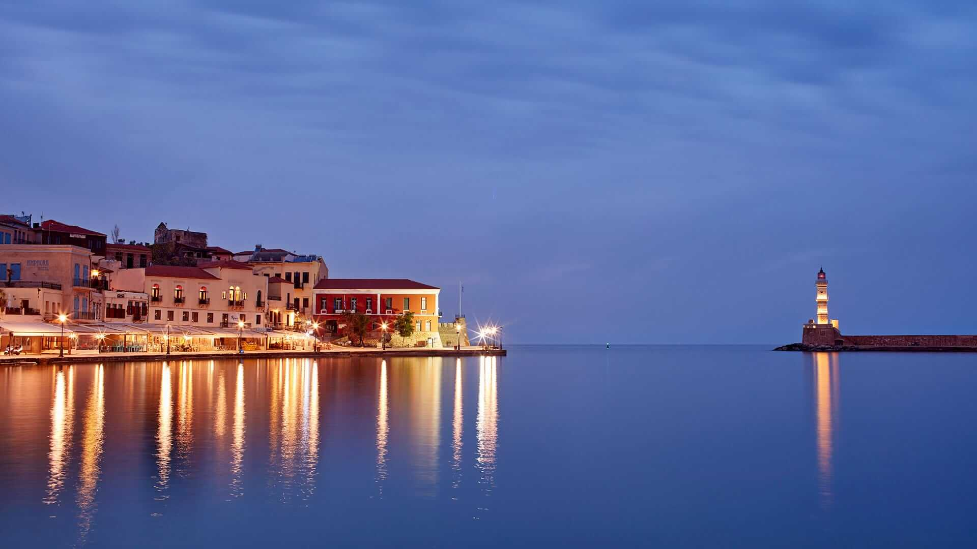 The stunning view of the sea, lighthouse, & Venetian harbour in Chania at dusk