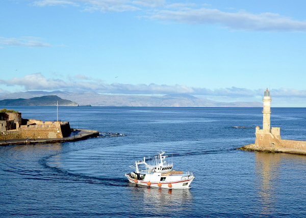 A boat enters Chania harbour on a boat cruise experience organised by Domus Renier Boutique Hotel