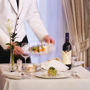 Waiter delivers a dish for the private in-suite dining experience at Domus Renier Hotel in Chania