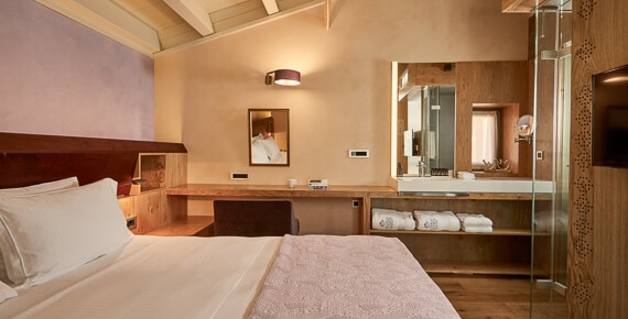 Bed & mirror in luxury Junior Suite with Outdoor Jacuzzi at Domus Renier Luxury Hotel in Chania